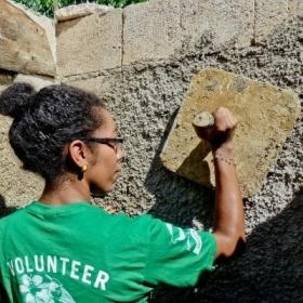 A Projects Abroad volunteer helps with plastering a wall during volunteer building work abroad.
